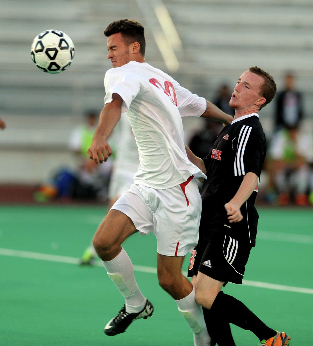 Central's Michele Muhaj heads the ball, during boys soccer action against Fairfield Warde in Bridgeport, Conn. on Wednesday September 18, 2013. At right is Fairfield Warde's Jack Anderson.