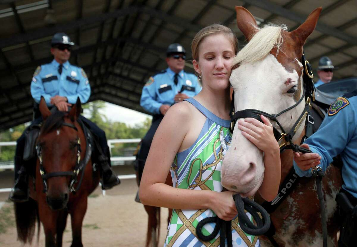 """Katherine Richards, 24, embraces """"Smash"""" after giving the Houston Police Foundation a $10,000 check to sponsor """"Smash"""" to become a the newest member of HPD Mounted Patrol on Wednesday, Sept. 18, 2013, in Houston. Katherine Richards spearheaded the fundraising efforts with her other special needs friends. The funds will sponsor """"Smash"""" for two years, and girls plan to continue to fundraise money for the deaf horse."""