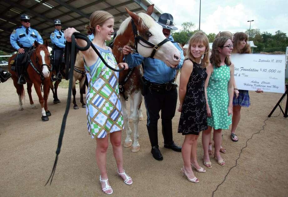 "Katherine Richards, 24, holds on to ""Smash"" as sponsors Ashley Billard, Meg Norman, and Christi Roberts give the Houston Police Foundation a $10,000 check. Photo: Mayra Beltran, Houston Chronicle / © 2013 Houston Chronicle"