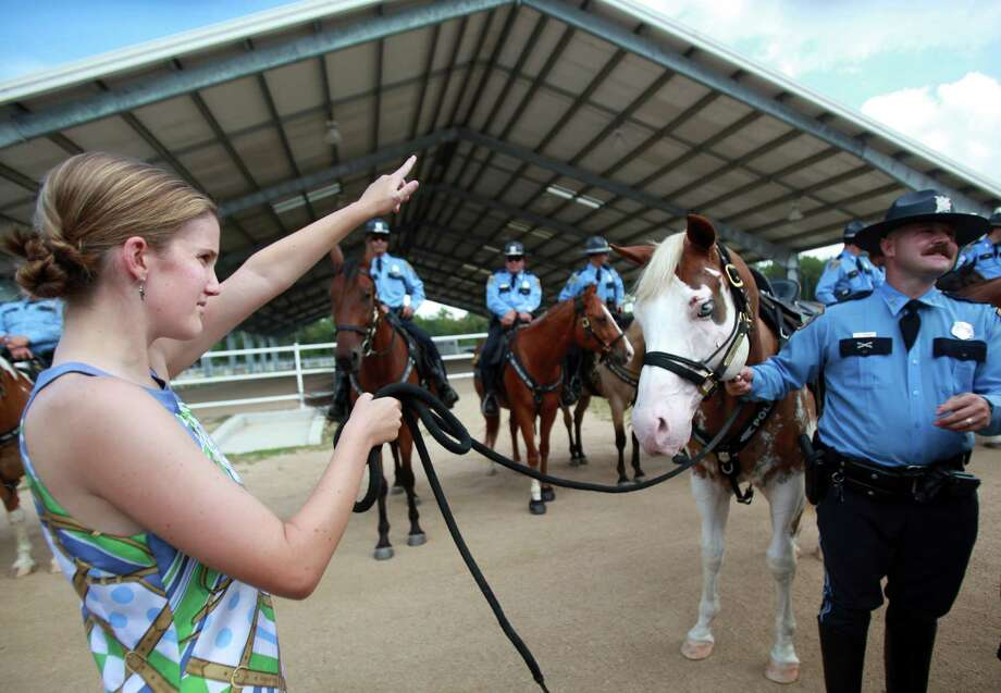 "Katherine Richards, 24, commands ""Smash"", as Officer Jeff Harris holds the reigns after a presentation at the HPD Mounted Patrol on Wednesday, Sept. 18, 2013, in Houston. Photo: Mayra Beltran, Houston Chronicle / © 2013 Houston Chronicle"