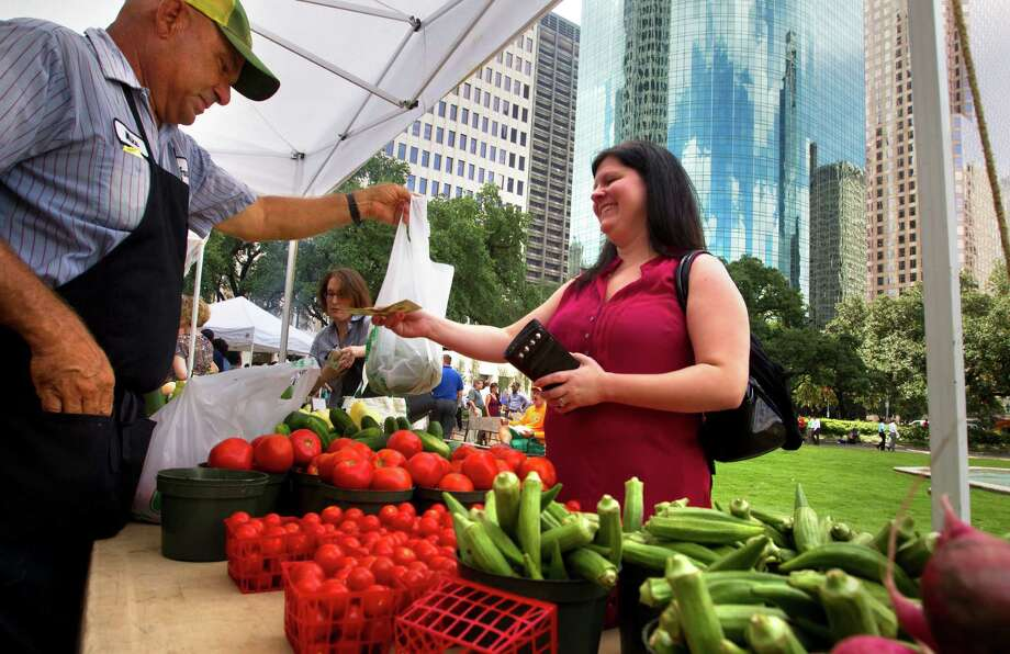 "Mike Atkinson of Atkinson Farms, left, hands Amie Schexnayder, right, her produce at the City Hall Farmer's Market, Wednesday, Sept. 18, 2013, in Houston. ""I've been waiting on it to open up,"" she said of the market. ""I look forward to coming down to get my produce weekly."" The market is open every Wednesday until December 18. Photo: Cody Duty, Houston Chronicle / © 2013 Houston Chronicle"