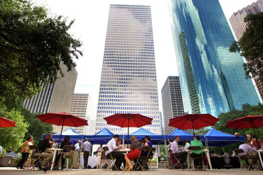 Customers eat food under umbrellas at the City Hall Farmer's Market. Photo: Cody Duty, Houston Chronicle / © 2013 Houston Chronicle