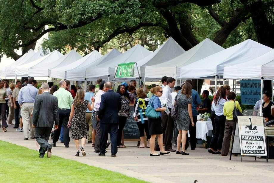 Customers walk through at the City Hall Farmer's Market in Houston. Photo: Cody Duty, Houston Chronicle / © 2013 Houston Chronicle