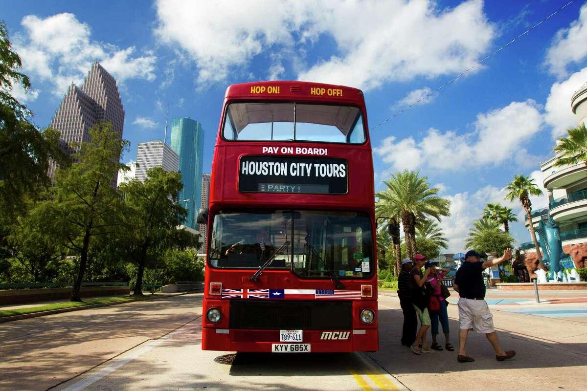 Passengers depart a new red double decker tour bus outside the Downtown Aquarium on Thursday, Sept. 12, 2013, in Houston.