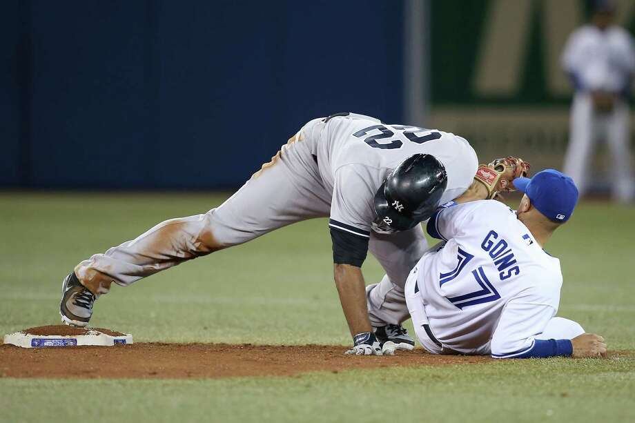 TORONTO, CANADA - SEPTEMBER 18: Vernon Wells #22 of the New York Yankees slides safely into second base with a two-run double in the eighth inning during MLB game action as Ryan Goins #17 of the Toronto Blue Jays tries to make the tag on September 18, 2013 at Rogers Centre in Toronto, Ontario, Canada. (Photo by Tom Szczerbowski/Getty Images) ORG XMIT: 163495613 Photo: Tom Szczerbowski / 2013 Getty Images