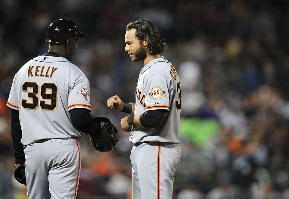 After singling home a run but getting thrown out trying for a double, Brandon Crawford talks to coach Roberto Kelly. Photo: Maddie Meyer, Getty Images