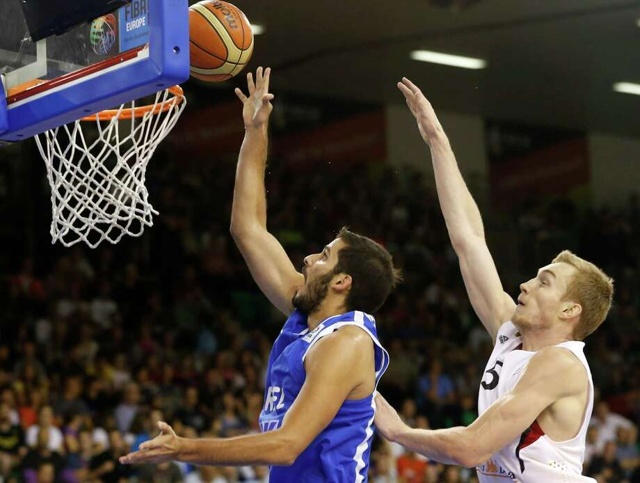 Germany's Niels Giffey, right, challenges for the ball with Israel's Omri Casspi, during their EuroBasket European Basketball Championship Group A match in Ljubljana, Slovenia, Monday, Sept. 9, 2013. (AP Photo/Darko Bandic) Photo: Darko Bandic, Associated Press / Associated Press