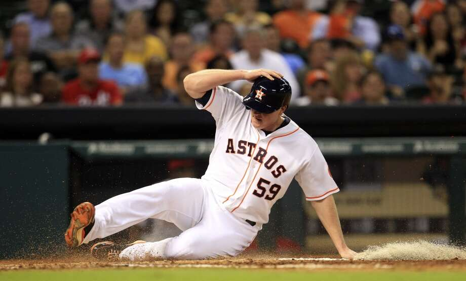 Astros left fielder Marc Krauss (59) scores a run on a sac fly by Carlos Corporan. Photo: Karen Warren, Houston Chronicle