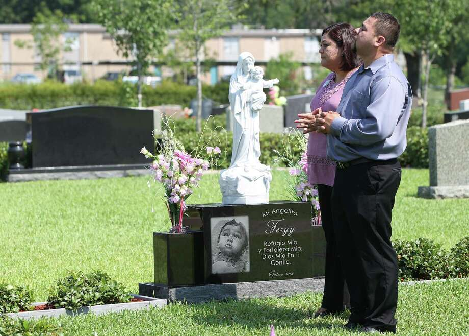 "Nancy and David Rodriguez visit their daughter Fernanda ""Fergy"" Rodriguez's grave. The family often gathers at the cemetery on weekends to have pizza or breakfast tacos with Fergy. Photo: Karen Warren, Houston Chronicle / © 2013 Houston Chronicle"