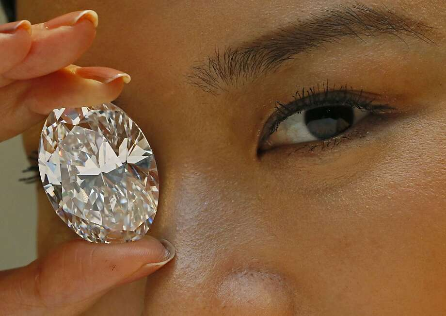 You could put an eye out with that: A 118.28-carat white diamond is displayed by a model at a press preview at Sotheby's auction house. The oval stone will be auctioned off in Hong Kong on Oct. 7 and has a pre-sale estimate of US$28 million to $35 million. The current record for any white diamond is US$26.7 million. Photo: Vincent Yu, Associated Press