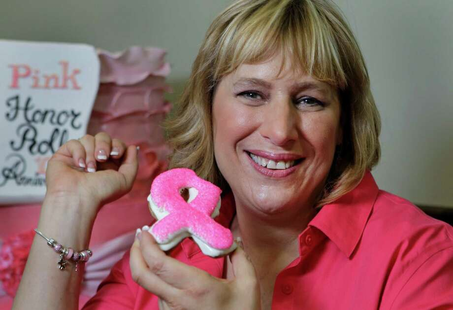 Janice Jucker poses at Three Brothers Bakery,4036 S Braeswood, Tuesday, Sept. 3, 2013, in Houston with a pink breast cancer ribbon cookie. She is a breast cancer survivor. ( Melissa Phillip / Houston Chronicle ) Photo: Melissa Phillip, Staff / © 2013  Houston Chronicle