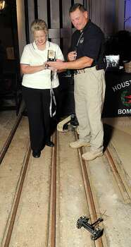 HPD senior officer and bomb technician Randy Schirck shows mayor Annise Parker how to use a remote vehicle at the HPD True Blue Gala benefitting the Houston Police Foundation in 2012. (Dave Rossman photo) Photo: Dave Rossman, Freelance / © 2012 Dave Rossman