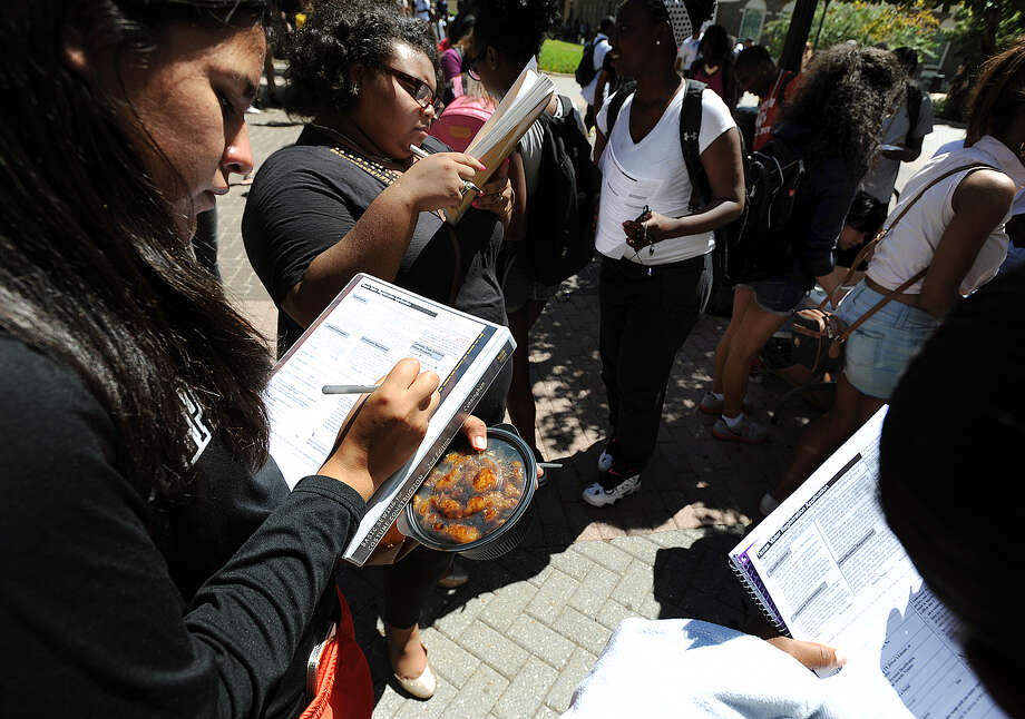 First-time voters  fill out voter registration forms during a campus registration event in  2012. Texas lawmakers have passed measures to make it more difficult to conduct voter registration drives. Photo: File Photo, Associated Press / THE DAILY SENTINEL