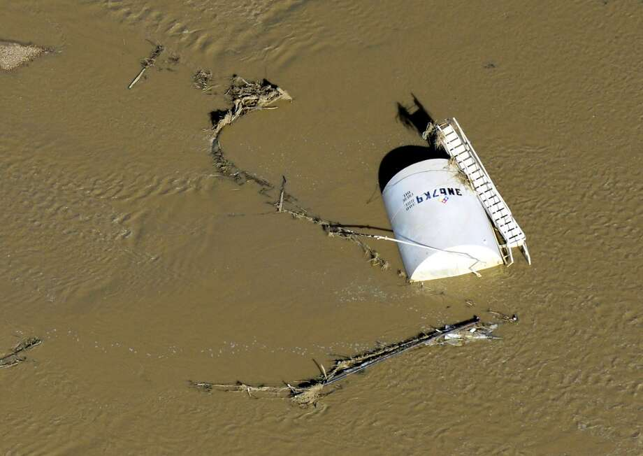 In this Sept. 17, 2013 photo, a crude oil storage tank lies on its side in flood water along the South Platte River, in Weld County, Colo. Hundreds of natural gas and oil wells along with pipelines are shut down by flooding, as state and federal inspectors gauge the damage and look for potential contamination from inundated oil fields. (AP Photo/John Wark) Photo: John Wark, Associated Press