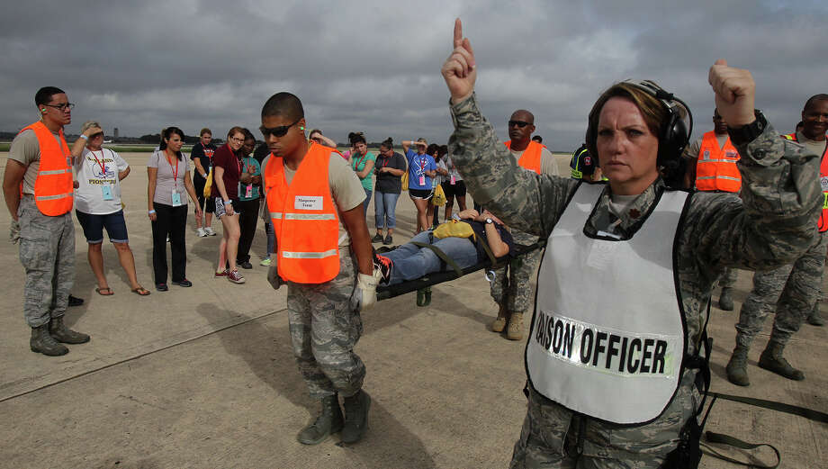 United States Air Force Major Connie LoBrutto (right) gives to go ahead to transport a nursing student playing the role of a mass casualty victim Thursday September 19, 2013 at an exercise at Hangar 1610 at Port San Antonio. The exercise, called San Antonio Mass Casualty Exercise Event or SAMCEE 2013, is a disaster scenario designed to test the ability of local hospitals to respond to a mass casualty event such as a tornado or other disaster. Photo: JOHN DAVENPORT, SAN ANTONIO EXPRESS-NEWS / ©San Antonio Express-News/Photo may be sold to the public
