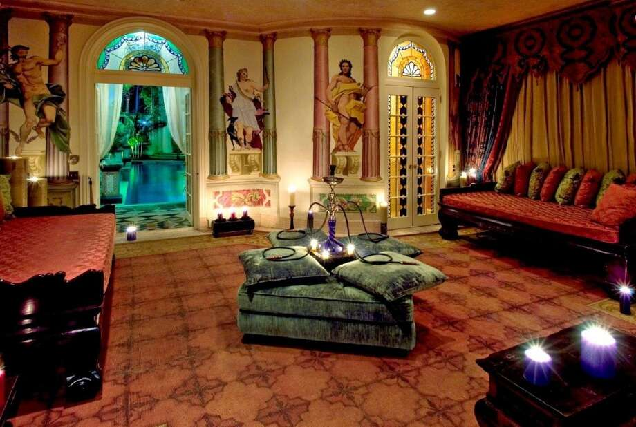 Living area with glimpse of glowing blue mystery room beyond.  Photo via Top 10 Real Estate Deals. Photo: Http://www.toptenrealestatedeals.com/gbrown/weekly-features/7-23-2013/