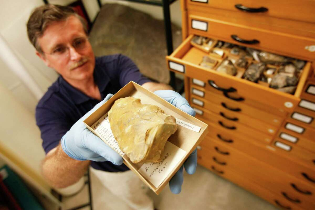 Dirk Van Tuerenhout, PhD, curator of anthropology, holds an ancient stone tool stored at the Museum of Natural Science's Marconi street warehouse, which will allow visitors, for a price, to tour same, Sept. 19, 2013 in Houston.