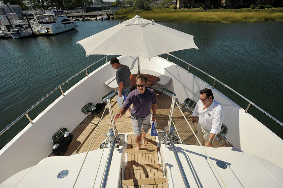 Michael Costa, right, with SeaNet, shows Bruce Masserman, center foreground, and Larry Schwartz around a $9.4 million 2013 Benetti Delfino yacht during the Norwalk Boat Show at the Norwalk Cove Marina in Norwalk, Conn., on Thursday, Sept. 19, 2013. The boat show will continue every day this week until Sunday with hours from 10 a.m.-6 p.m. Photo: Jason Rearick / Stamford Advocate