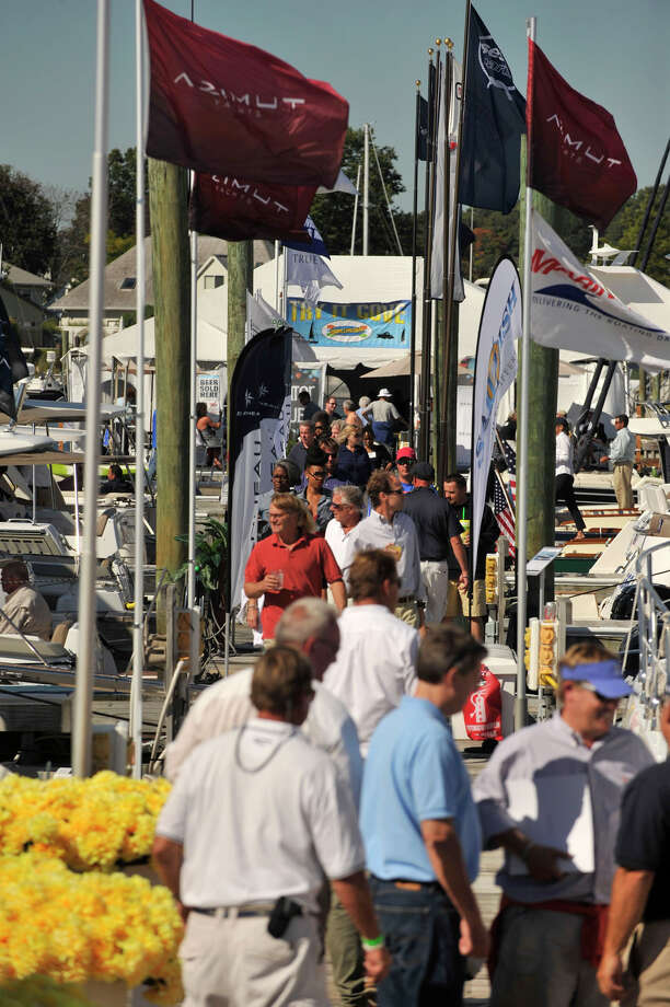 People walk along one of the three docks featuring boats in the water during the Norwalk Boat Show at the Norwalk Cove Marina in Norwalk, Conn., on Thursday, Sept. 19, 2013. The boat show will continue every day this week until Sunday with hours from 10 a.m.-6 p.m. Photo: Jason Rearick / Stamford Advocate