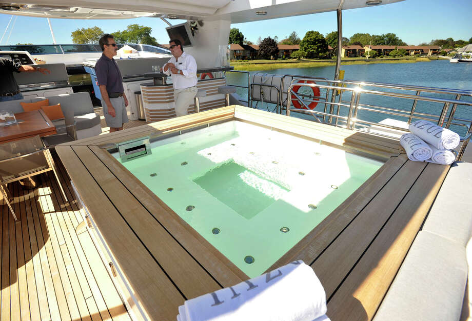 Michael Costa, top right, with SeaNet, shows Bruce Masserman around the top deck of a $9.4 million 2013 Benetti Delfino yacht that features a hot tub during the Norwalk Boat Show at the Norwalk Cove Marina in Norwalk, Conn., on Thursday, Sept. 19, 2013. The boat show will continue every day this week until Sunday with hours from 10 a.m.-6 p.m. Photo: Jason Rearick / Stamford Advocate