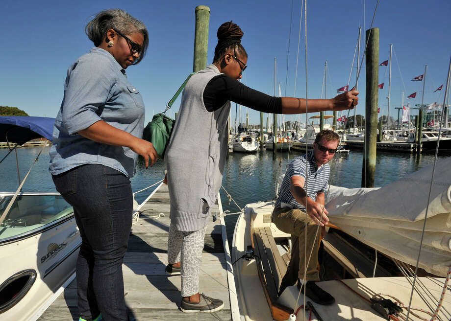 Ty Alexander, left, and Yoli Ouiya board a small sailboat with the help of Sean Hussey with Sound Sailing Center before taking it out for a short ride during the Norwalk Boat Show at the Norwalk Cove Marina in Norwalk, Conn., on Thursday, Sept. 19, 2013. The boat show will continue every day this week until Sunday with hours from 10 a.m.-6 p.m. Photo: Jason Rearick / Stamford Advocate