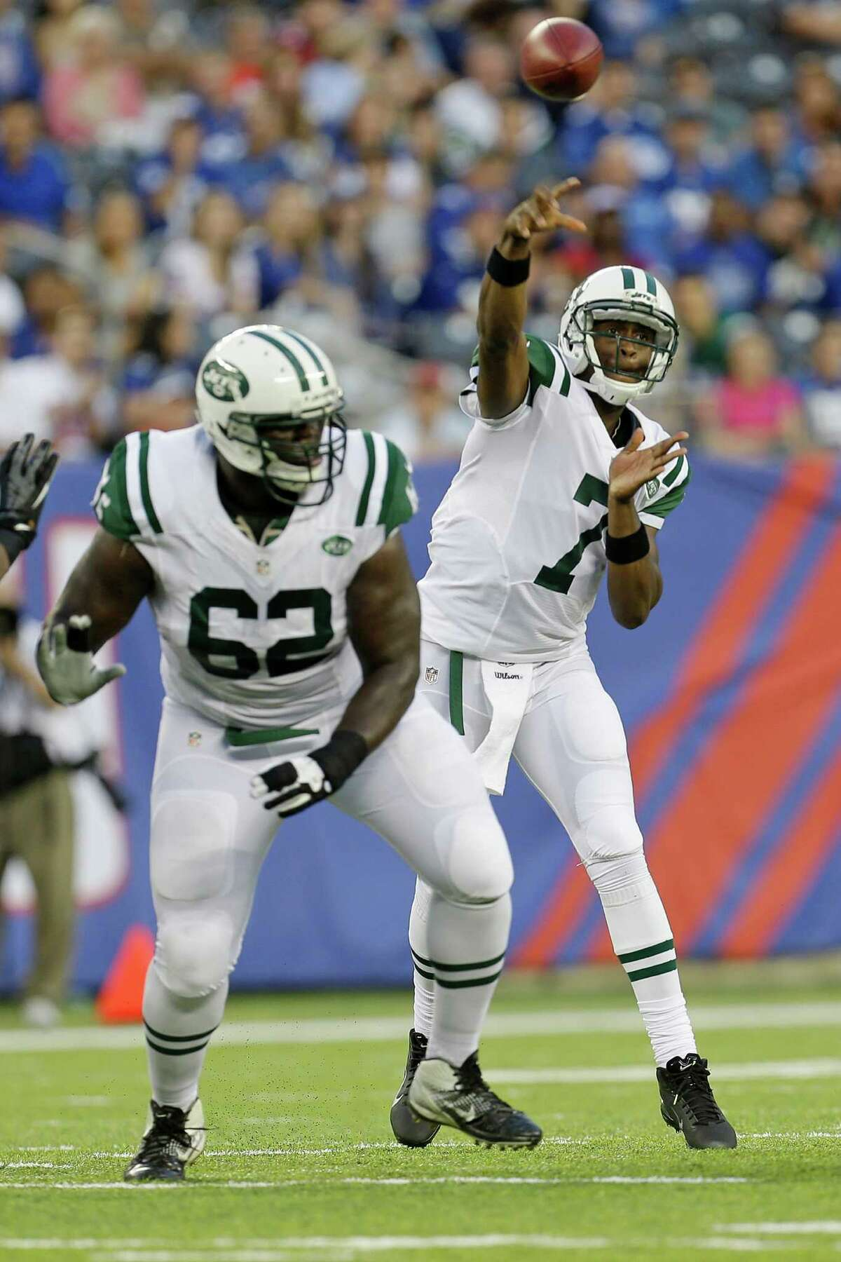 New York Jets quarterback Geno Smith (7) throws a pass over guard Vladimir Ducasse (62) during the first half of a preseason NFL football game against the New York Giants Saturday, Aug. 24, 2013, in East Rutherford N.J.