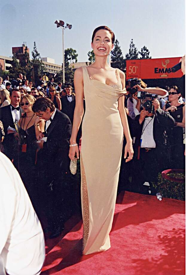 "Hit: Angelina Jolie, 1998. Before Jolie was one half of Brangelina and known as much for her humanitarian work as for her acting, she walked the red carpet as an Emmy nominee for ""Gia"" in this sleek, nude-colored  Randolph Duke dress. Photo: Jeff Kravitz, FilmMagic"