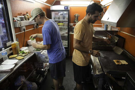 Proprietors Andrew Samia, left, and Shane Reed at work inside Crazy Carl's at the food truck park at Boardwalk on Bulverde.