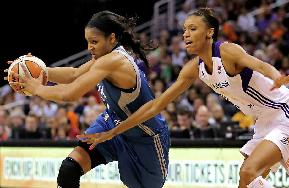 FILE - In this June 19, 2013, file photo, Minnesota Lynx guard Maya Moore, left, drives past Phoenix Mercury forward Dewanna Bonner during a WNBA basketball game in Phoenix. Moore and the Lynx won a title in her first season and reached the finals again in her second season, an incredibly successful start by any measure. For those expecting Moore to take the league by storm and dominate from the start, they had to wait a bit. Three years, to be exact. Now in her third season, Moore has taken over. (AP Photo/Matt York, File) Photo: Matt York, Associated Press / Associated Press