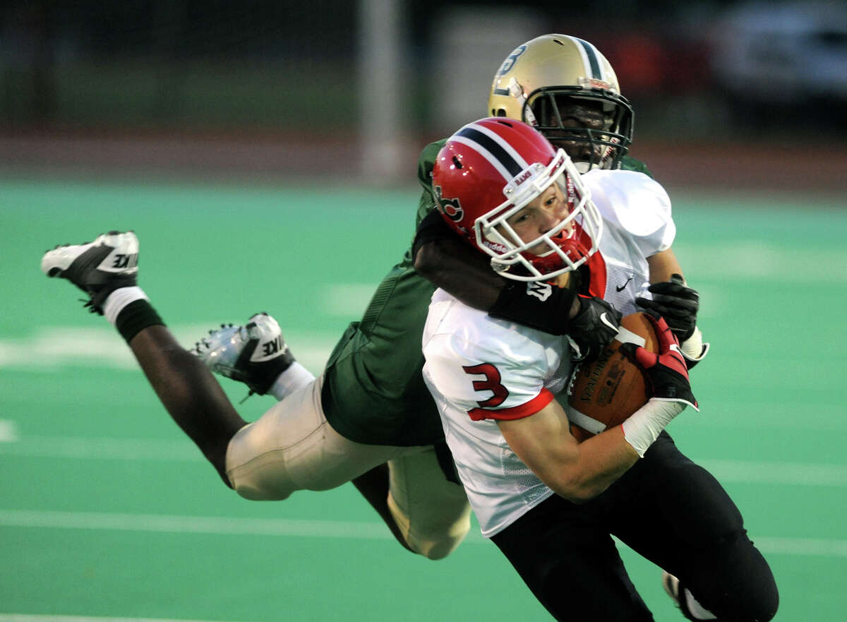 Bassick's Kenny Rene leaps onto New Canaan's Jack Gilio to make the tackle, during high school football action in Bridgeport, Conn. on Thurssday September 19, 2013.