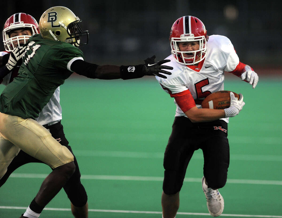 Bassick's Kenny Rene reaches out to grab New Canaan's Graham Wagner, right, during high school football action in Bridgeport, Conn. on Thurssday September 19, 2013.