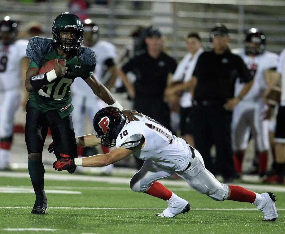 Kingwood Park's Carveon Bluiett (30) evades the tackle of Porter's Brandon Skidgel (10) as he gains yardage up the field during the fourth quarter of the Porter-Kingwood Park High School football game at Turner Stadium, Thursday, Sept. 19, 2013, in Humble. Photo: Karen Warren, Houston Chronicle / © 2013 Houston Chronicle