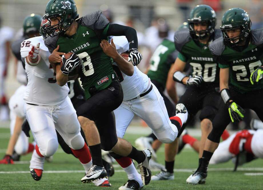 Kingwood Park's Caleb Lewallen (8) runs the ball against Porter's Mark Adame (32) and Colby Cluse (30) during the first quarter of the Porter-Kingwood Park High School football game at Turner Stadium, Thursday, Sept. 19, 2013, in Humble. Photo: Karen Warren, Houston Chronicle / © 2013 Houston Chronicle