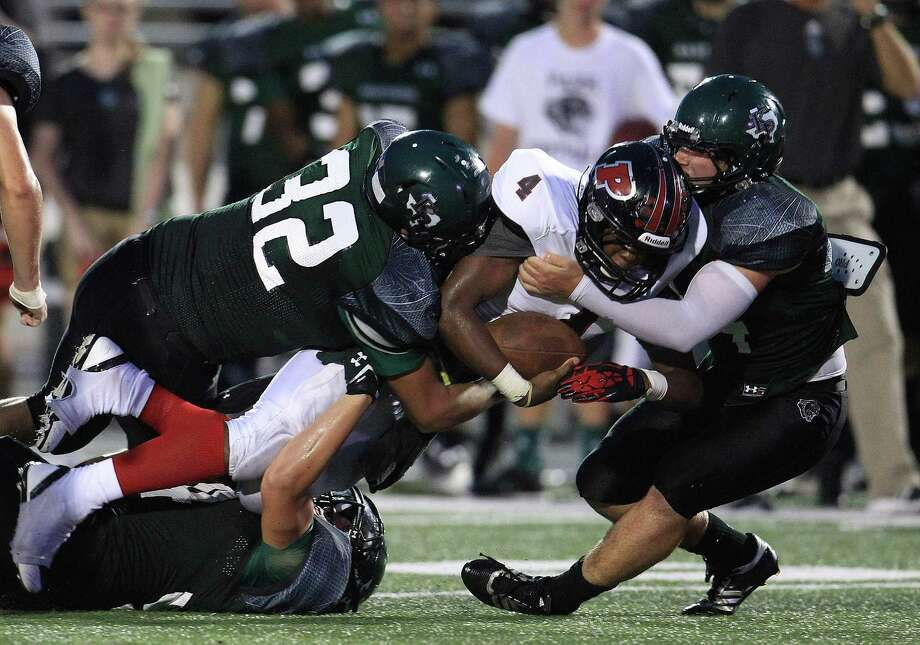 Porter's Marlon Lewis (4) gets tackled by Kingwood Park's defense during the first half of the Porter-Kingwood Park High School football game at Turner Stadium, Thursday, Sept. 19, 2013, in Humble. Photo: Karen Warren, Houston Chronicle / © 2013 Houston Chronicle