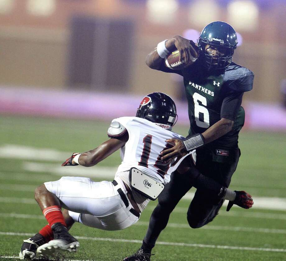 Porter's Noah Simon (14) tries to tackle Kingwood Park's QB Jaylon Henderson (6) on a quarterback keeper during the second quarter of the Porter-Kingwood Park High School football game at Turner Stadium, Thursday, Sept. 19, 2013, in Humble. Photo: Karen Warren, Houston Chronicle / © 2013 Houston Chronicle