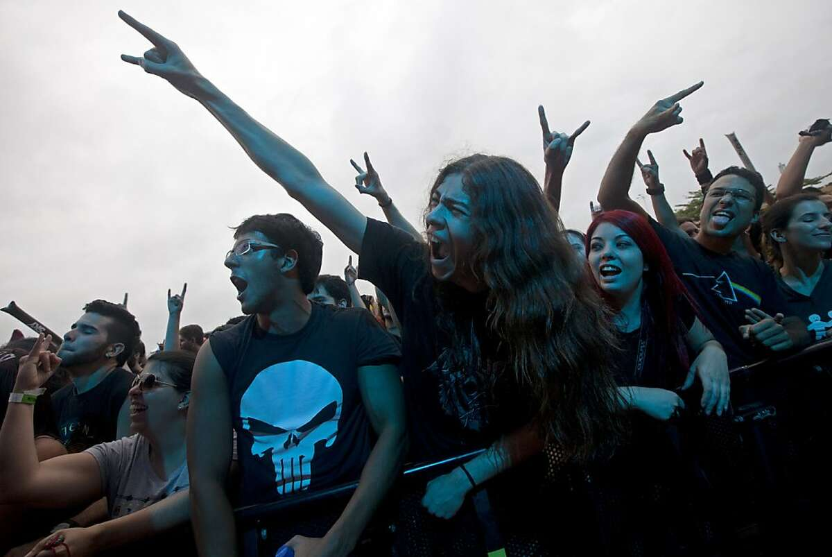 Fans sing along with the Brazilian band Almah during the annual Rock in Rio music festival in Rio de Janeiro, Brazil, Thursday, Sept. 19, 2013. The week long festival will feature a list of headliners including, Bon Jovi, Iron Maiden and Bruce Springsteen. (AP Photo/Silvia Izquierdo)