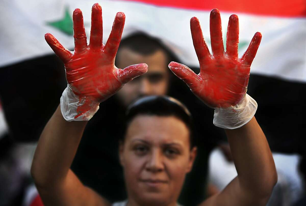 A Lebanese pro-Syrian regime supporter, with their hands painted in red to symbolize blood, attends a demonstration against a possible military strike in Syria, near the U.S. Embassy in Aukar, east of Beirut, Lebanon, Friday, Sept. 6, 2013. The prospect of a U.S.-led strike against Syria has raised concerns of potential retaliation from the Assad regime or its allies. The State Department ordered nonessential U.S. diplomats to leave Lebanon over security concerns and urged private American citizens to depart as well. (AP Photo/Hussein Malla)