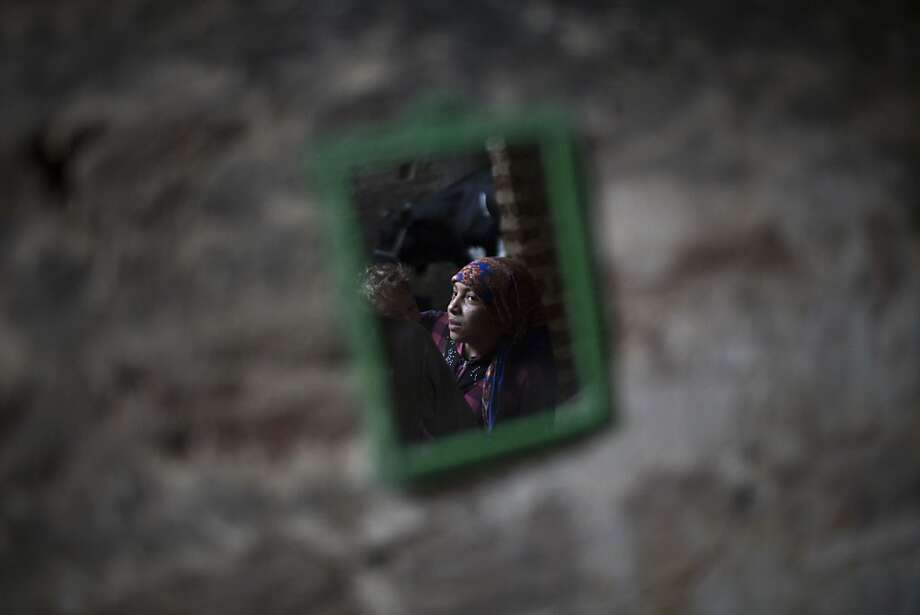 In this Sept. 17, 2013 photo, an Egyptian Coptic girl is reflected in a mirror at a house in a Christian area of Dalga, south of Cairo. Even after the military and police stormed Dalga to wrest it from control of Islamic militants, the town's Christians fear the protection won't last and that a worse retaliation by hard-liners is still to come. (AP Photo/Manu Brabo) Photo: Manu Brabo, Associated Press
