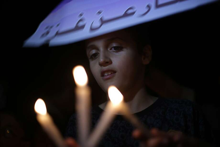 TOPSHOTS A Palestinian child holds candles during a vigil against the ongoing blockade and constant power cuts in Gaza City on September 19, 2013. The blockade, which left hundreds of Palestinians stranded on both sides of the crossing, followed widespread unrest in Egypt after a bloody crackdown by security forces on loyalists of ousted Islamist president Mohamed Morsi.    TOPSHOTS/AFP PHOTO / MOHAMMED ABEDMOHAMMED ABED/AFP/Getty Images Photo: Mohammed Abed, AFP/Getty Images