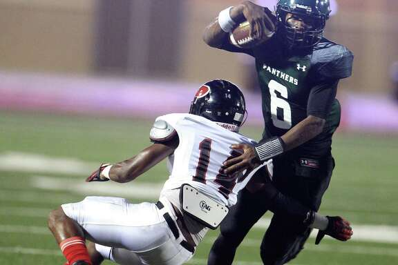 Kingwood Park quarterback Jaylon Henderson, right, was a handful for Noah Simon and the New Caney Porter defense Thursday night at Turner Stadium. Henderson threw four TD passes and ran for another score.