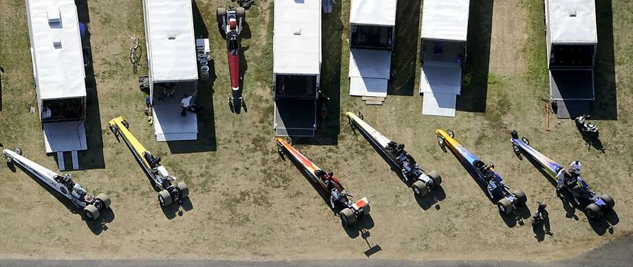 Dragsters in the super pro class sits in the pit area outside of their haulers Thursday afternoon, Sept. 19, 2013, as drivers wait their turn on the drag strip in the first round of the gamblers race as the Numidia Dragway hosts the NHRA Division I Bracket Finals through Saturday in Numidia, Pa. (AP Photo/Bloomsburg Press Enterprise, Jimmy May) Photo: Jimmy May, Associated Press
