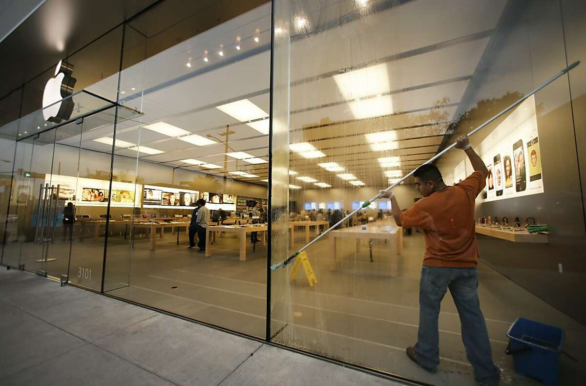 A Apple store employee washes the windows by the store entrance, Thursday, Sept. 19, 2013, in Dallas. Apple is schedule to release their iPhone 5S on Friday. (AP Photo/Tony Gutierrez)
