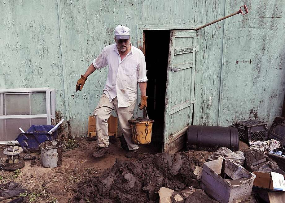 Ron West cleans mud out of his shed in Lyons, Colo., on Thursday, Sept. 19, 2013. His home was spared by floodwaters. The recovery process has begun all along the front range as people clean out flooded homes and businesses. Local governments are starting to clear debris and repair infrastructure.(AP Photo/Chris Schneider) Photo: Chris Schneider, Associated Press