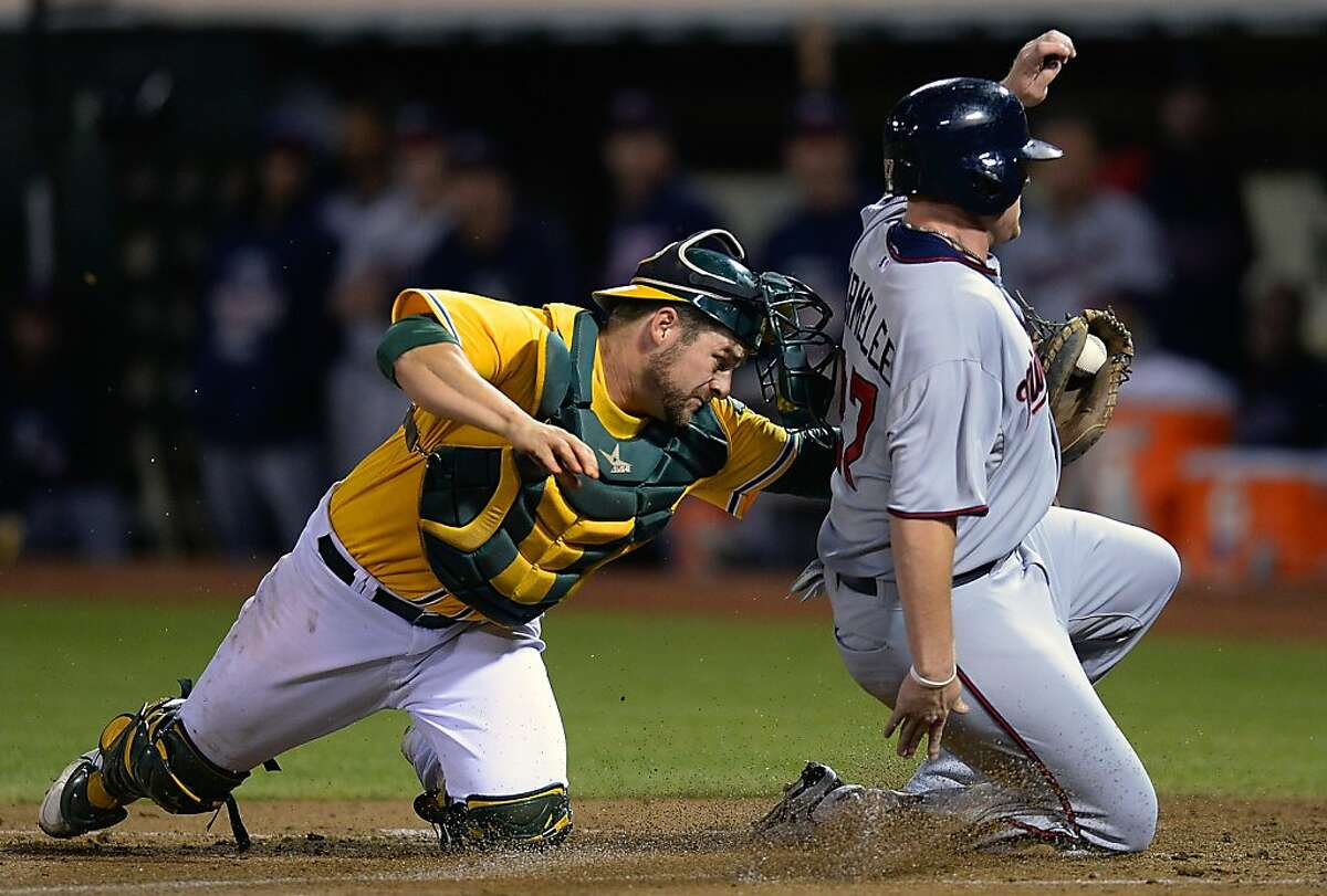 Chris Parmelee #27 of the Minnesota Twins scores on a fielder's choice, sliding under the tag of Stephen Vogt #21 of the Oakland Athletics during the third inning at O.co Coliseum on September 19, 2013 in Oakland, California. (Photo by Thearon W. Henderson/Getty Images)