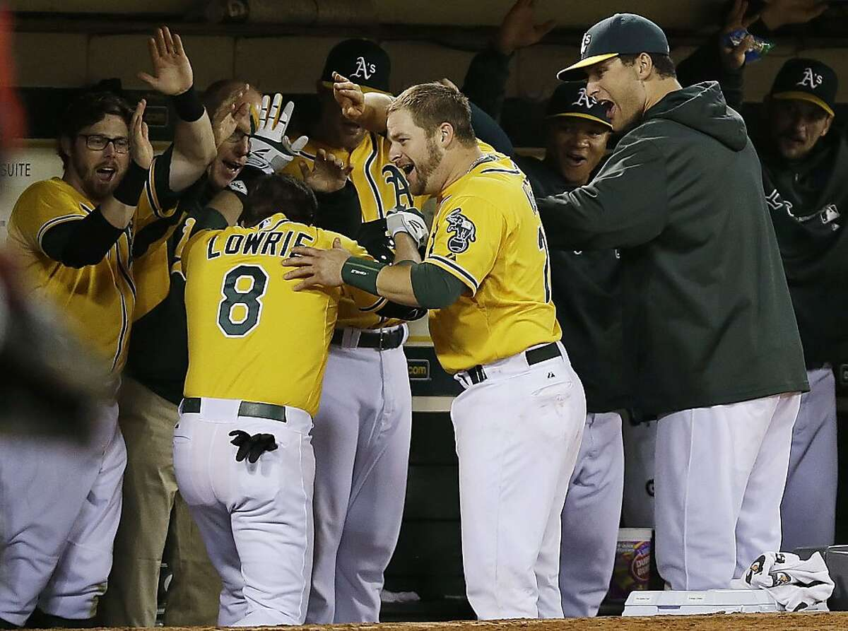 Oakland Athletics' Jed Lowrie (8) celebrates with teammates in the dugout after hitting a three-run home run against the Minnesota Twins during the sixth inning of a baseball game on Thursday, Sept. 19, 2013, in Oakland, Calif. (AP Photo/Marcio Jose Sanchez)