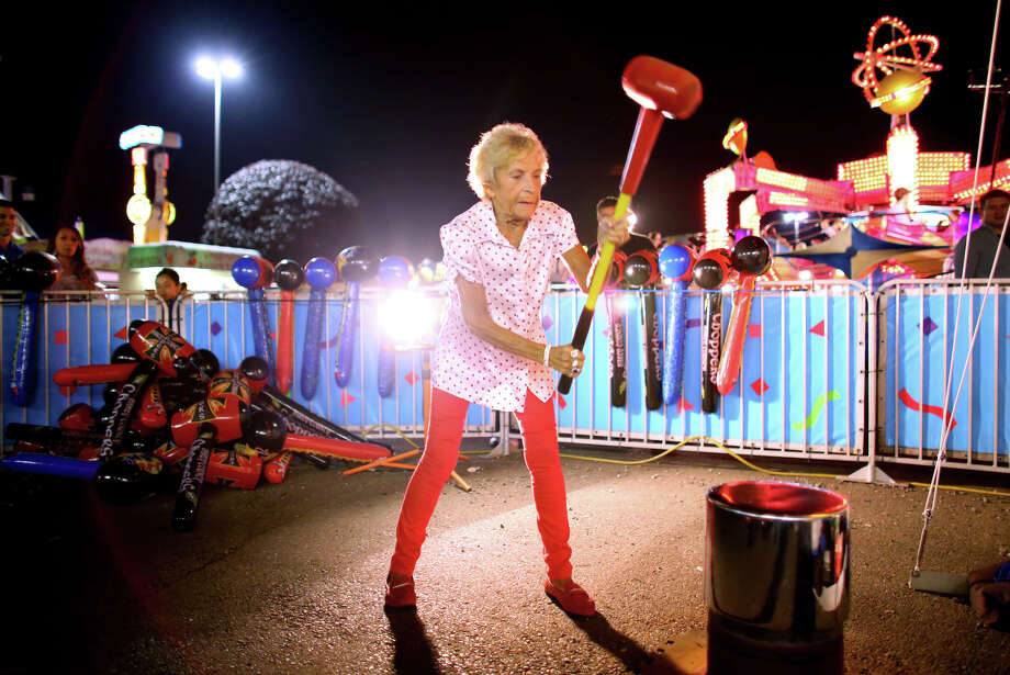 Bobbie Stogsdill, 72, swings a heavy mallet while trying to win a prize while playing the High Striker game on the midway at the 2013 Washington State Fair in Puyallup. The Washington State Fair, formerly known as the Puyallup Fair, has drawn large crowds each day since it opened on Sept. 6. The Fair continues through Sunday, Sept. 22. Photo: JOSHUA TRUJILLO, SEATTLEPI.COM / SEATTLEPI.COM