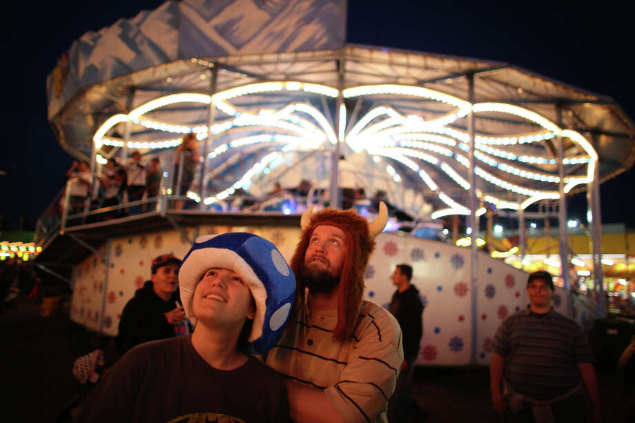 Rebecca and Michael Brown watch a ride spin high overhead during the 2013 Washington State Fair in Puyallup. The Washington State Fair, formerly known as the Puyallup Fair, has drawn large crowds each day since it opened on Sept. 6. The Fair continues through Sunday, Sept. 22nd. Photo: JOSHUA TRUJILLO, SEATTLEPI.COM / SEATTLEPI.COM