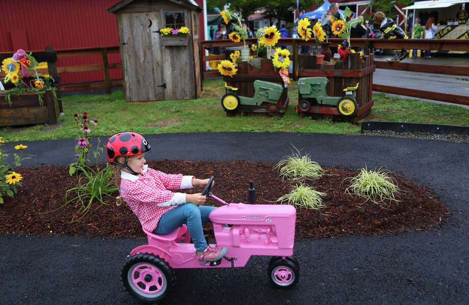 Iris Casswell, 4, rides a tractor during the 2013 Washington State Fair in Puyallup. The Washington State Fair, formerly known as the Puyallup Fair, has drawn large crowds each day since it opened on Sept. 6. The Fair continues through Sunday, Sept. 22. Photo: JOSHUA TRUJILLO, SEATTLEPI.COM / SEATTLEPI.COM