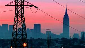 The Empire State Building towers over the skyline of a blackout-darkened New York City just before dawn in August 2003.  Power lines from Jersey City, N.J., are in foreground. Ten years after a blackout cascading from Ohio affected 50 million people, utilities and analysts say changes made in the aftermath make a similar outage unlikely today, though shifts in where and how power is generated raise new reliability concerns for the U.S. electric grid system.