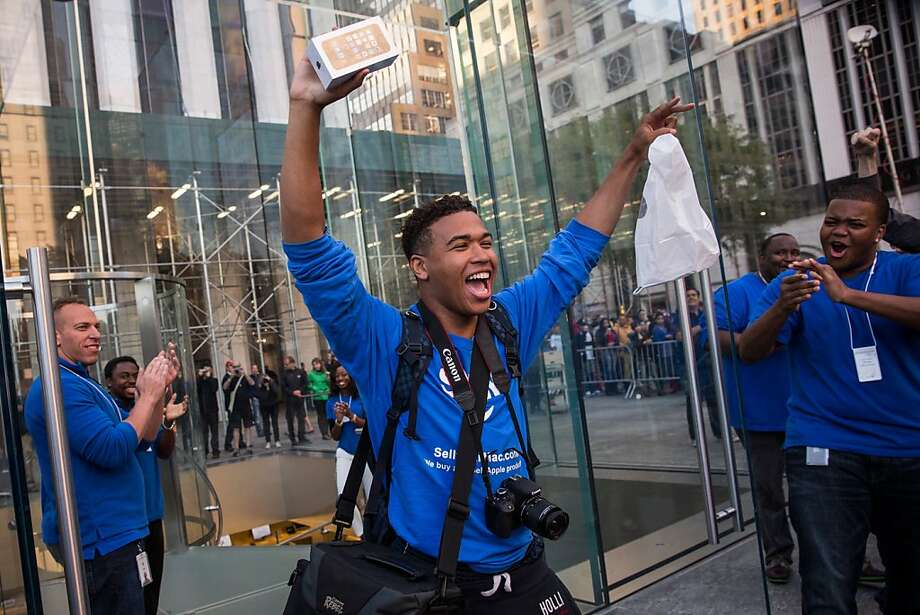 Brian Ceballo, who waited outside the Fifth Avenue Apple store for two weeks, walks out of the store after being the first person to buy an iPhone 5S on Friday, Sept. 20 in New York City. Apple launched two new models of iPhone: the iPhone 5S, which is preceded by the iPhone 5, and a cheaper, paired down version, the iPhone 5C. The phones come with a new operating system. Photo: Andrew Burton, Getty Images